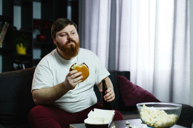 Толстый мужчина ест за столом