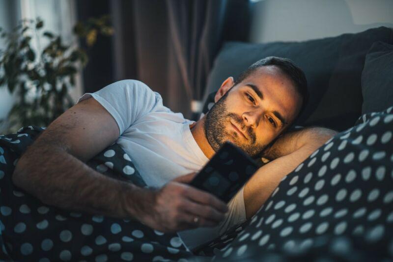 Мужчина пользуется телефоном в кровати