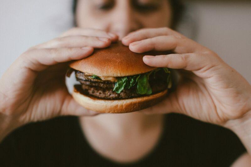 Мужчина с гамбургером в руках