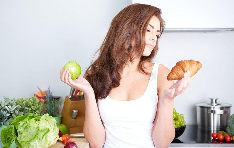Женщина с круассаном и яблоком