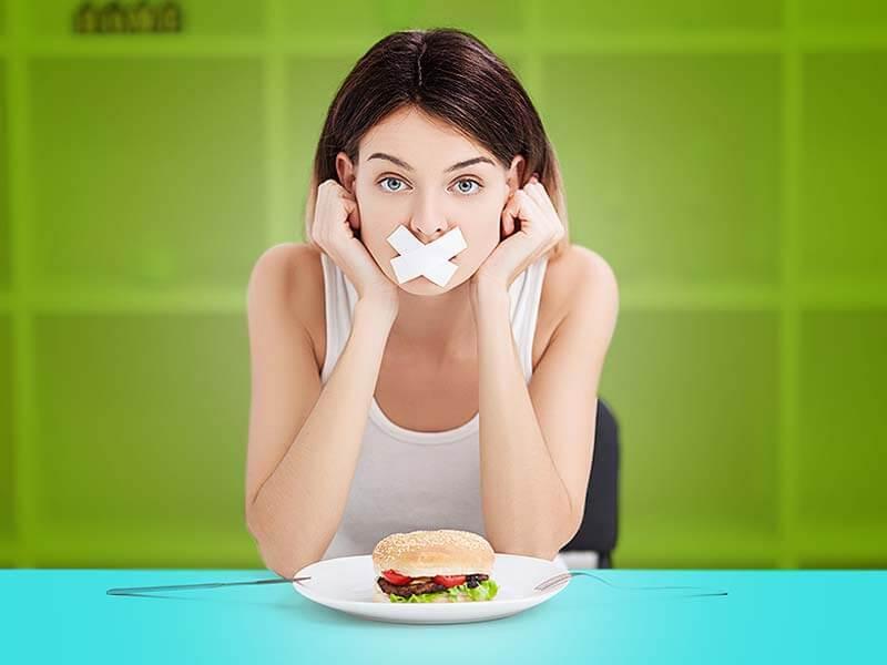 Женщина перед тарелкой с заклеенным ртом