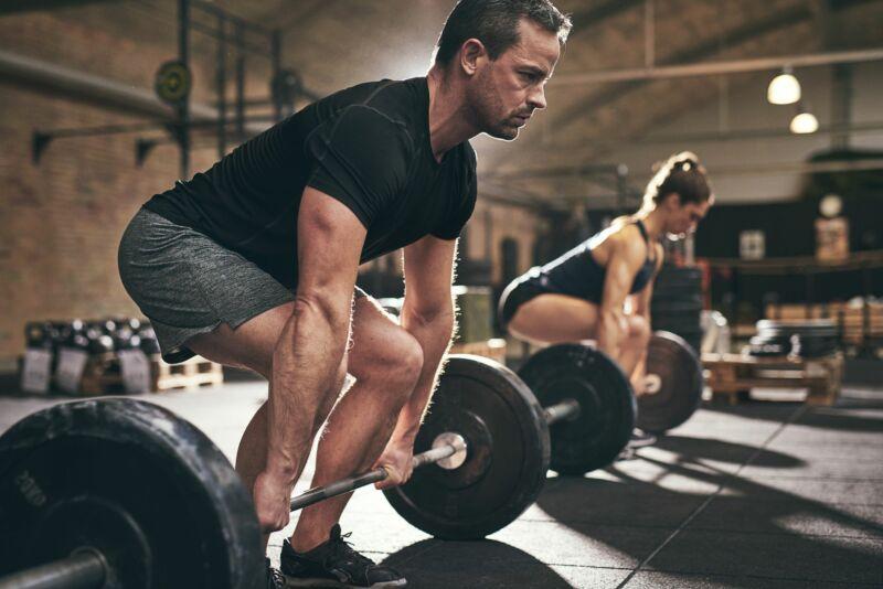 Мужчина и женщина делают становую тягу