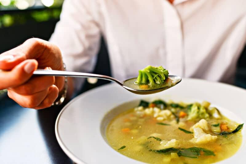 Мужчина ест суп