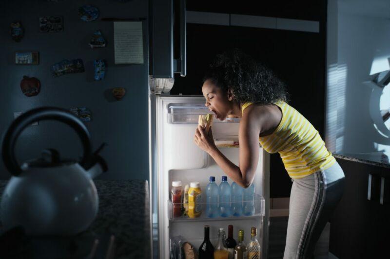 Женщина заглядывает в холодильник ночью