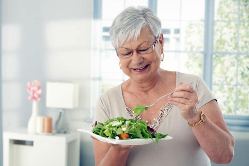 Старая женщина кушает салат