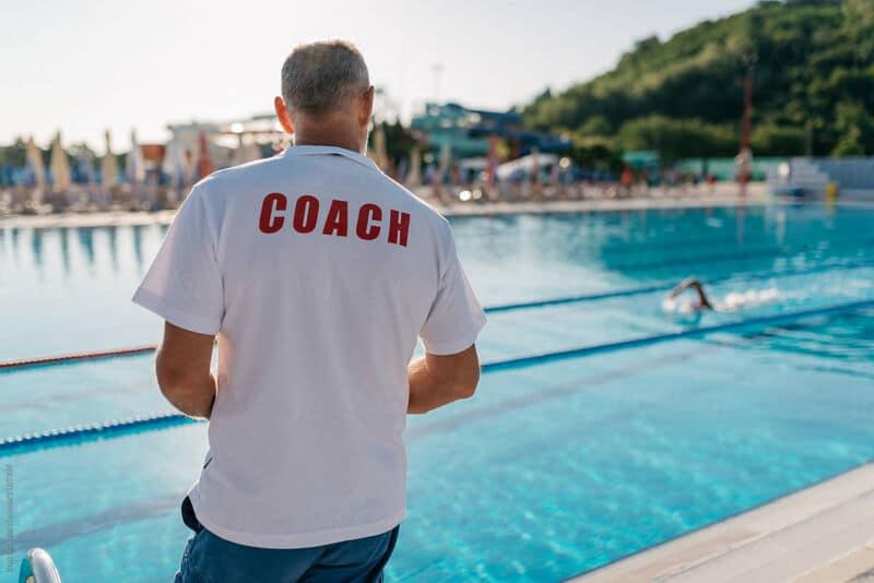 Тренер наблюдает за пловцами в бассейне
