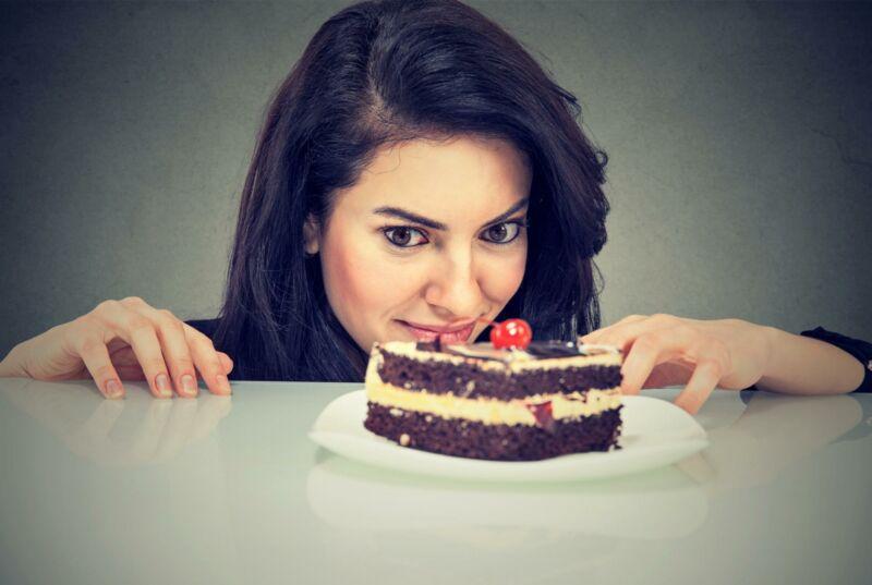 Женщина смотрит на кусок торта