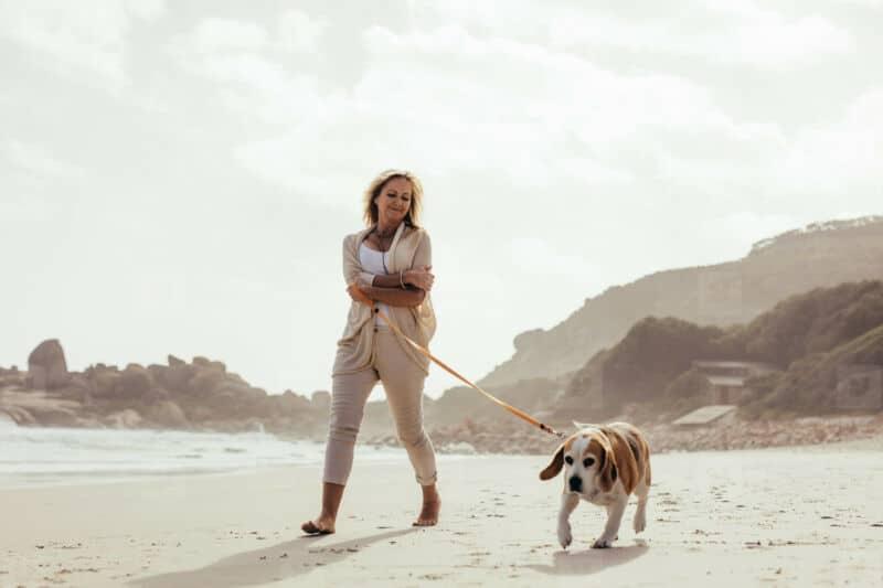 Женщина с собакой гуляет по пляжу