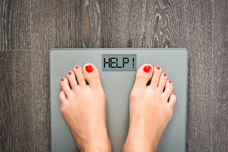 Женщина стоит на весах с надписью HELP