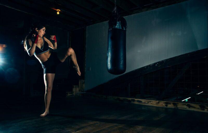 Женщина занимается кикбоксингом