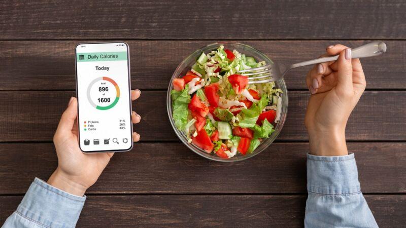 Миска с салатом и телефон с его калорийностью