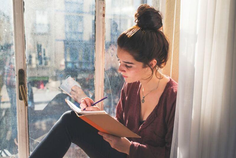 Женщина делает записи в дневник у окна