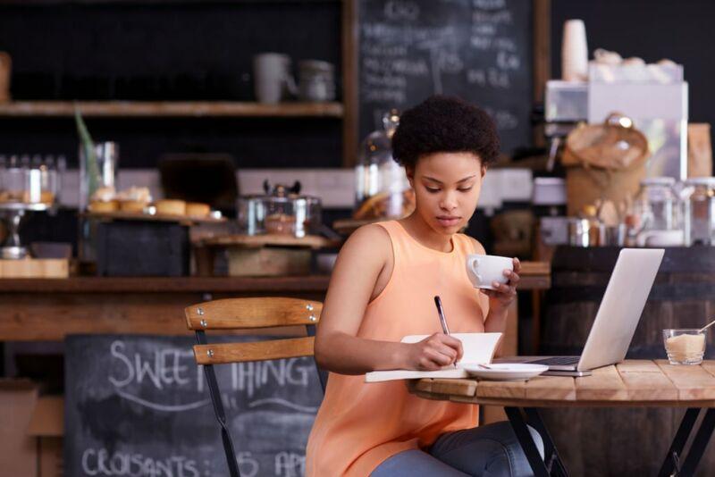 Женщина за столиком в кафе делает записи в дневник