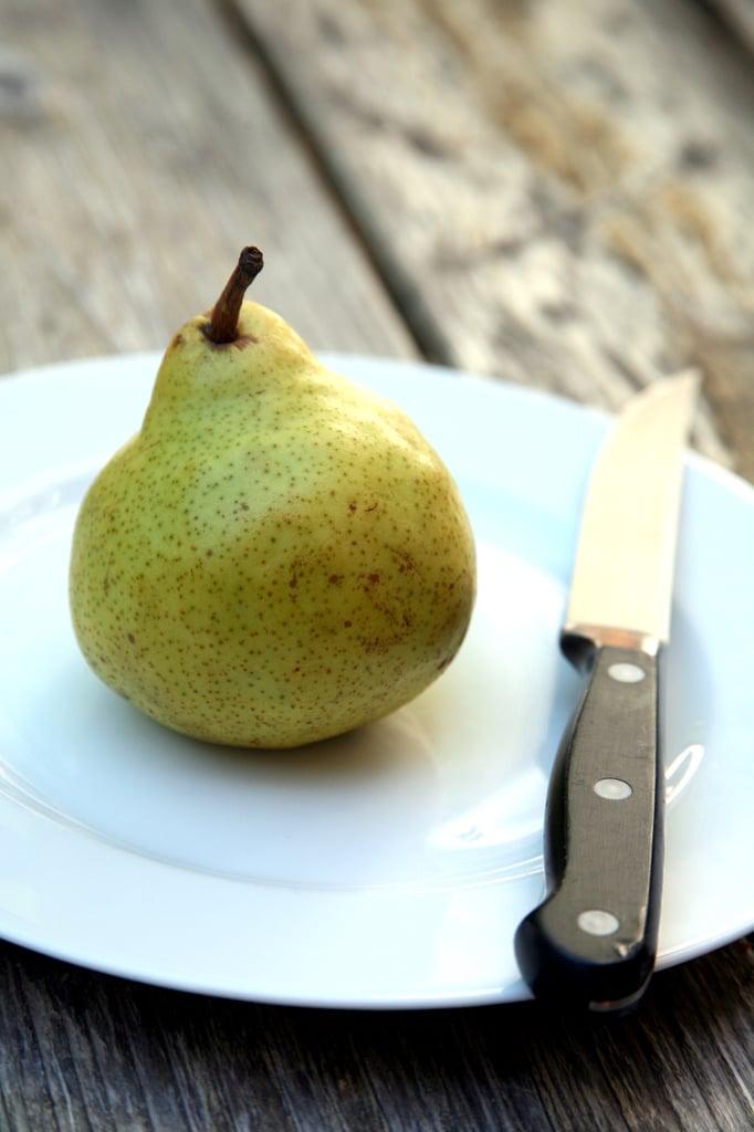 Целая груша на тарелке