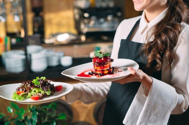 Официант принес тарелки с едой