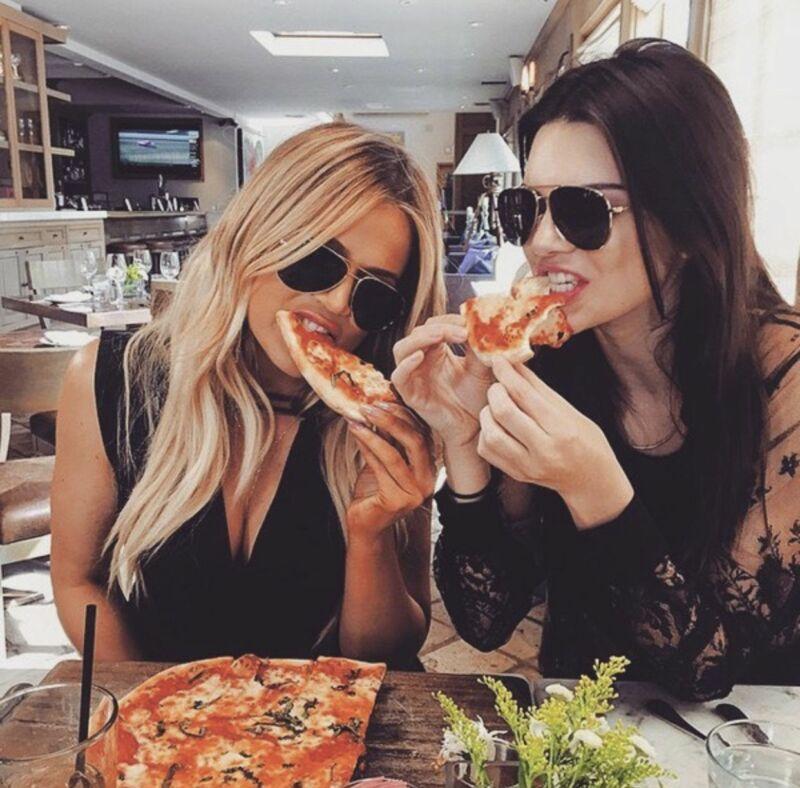 Женщины едят пиццу