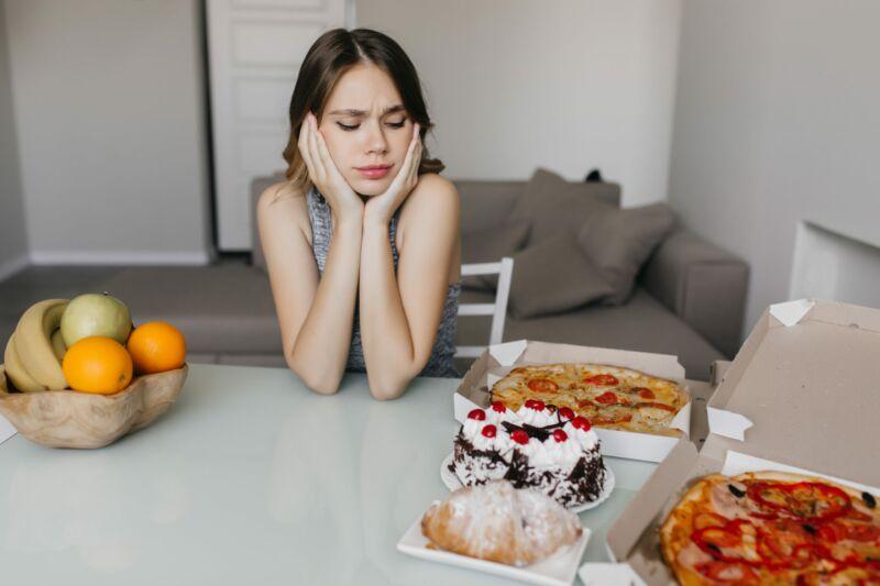 Женщина смотрит на торт и пиццу