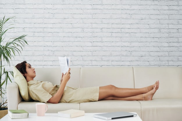 Женщина читает книгу на диване