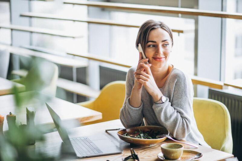 Женщина обедает и разговаривает по телефону