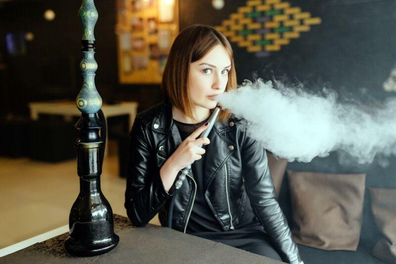 Женщина курит кальян