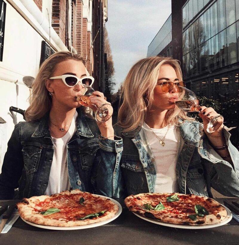 Женщины пьют вино и едят пиццу