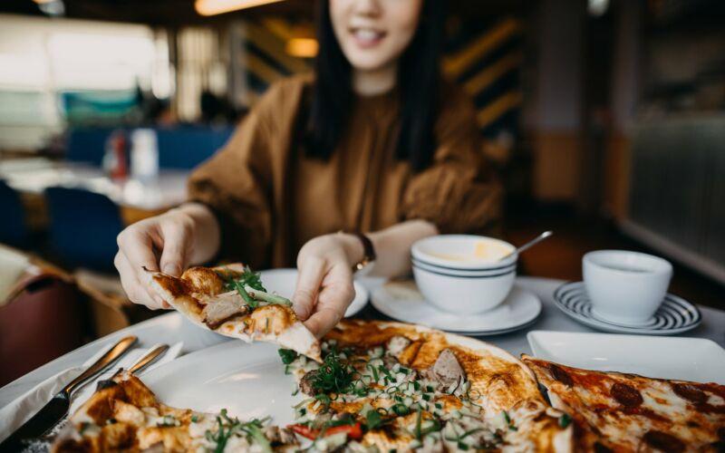 Женщина ест пиццу