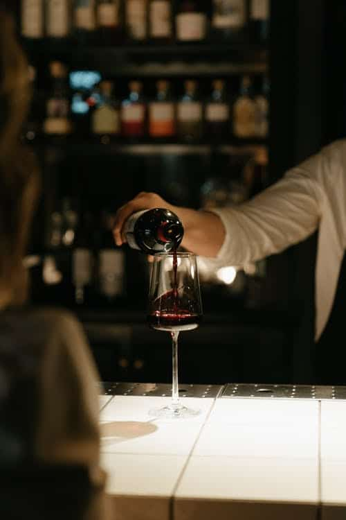 Бармен наливает бокал красного вина