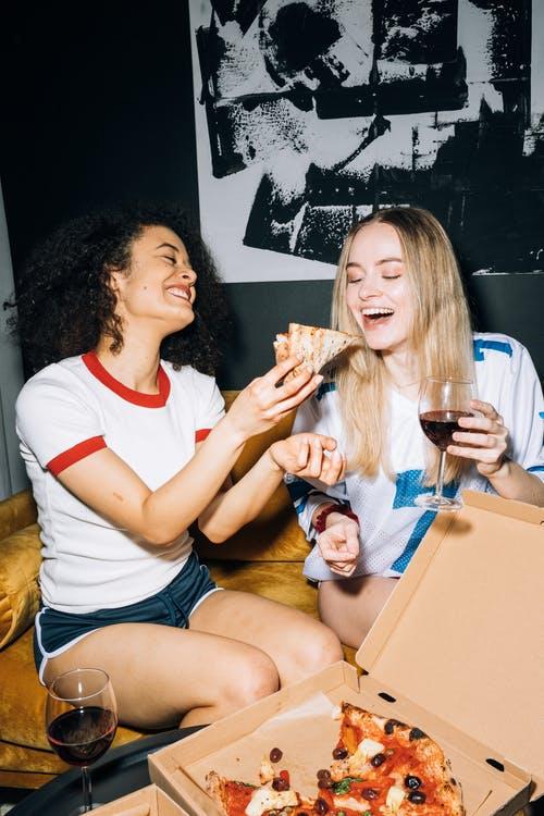 Девушки едят пиццу и пьют красное вино