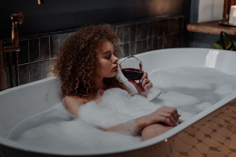 Женщина в ванной пьет красное вино