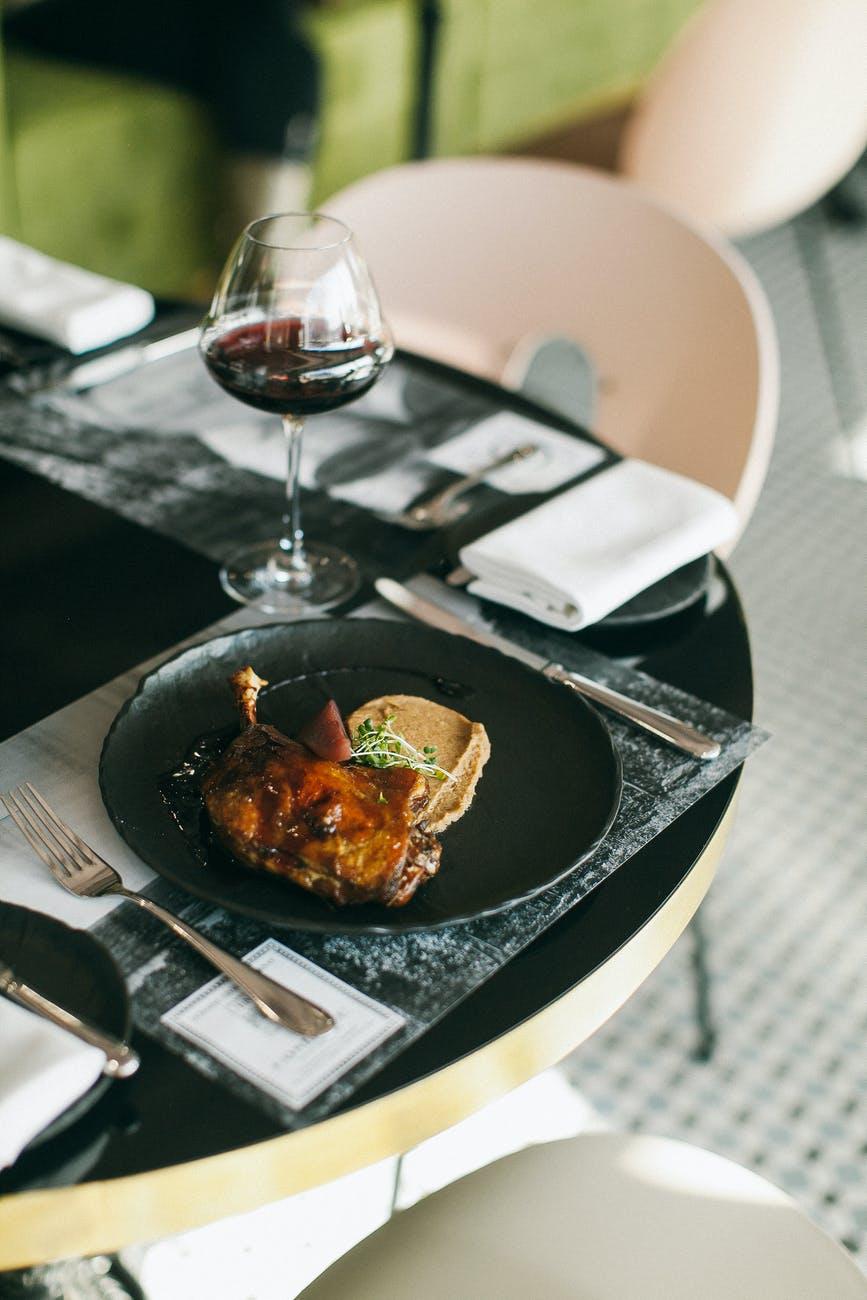 Бокал красного вина и еда в тарелке