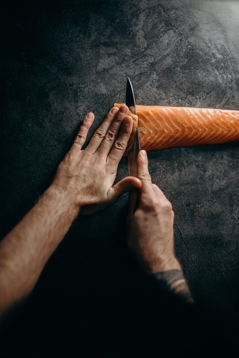 Мужчина нарезает лосось