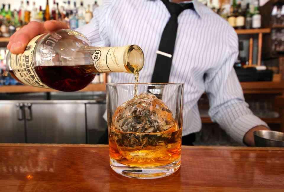 Бармен наливает виски