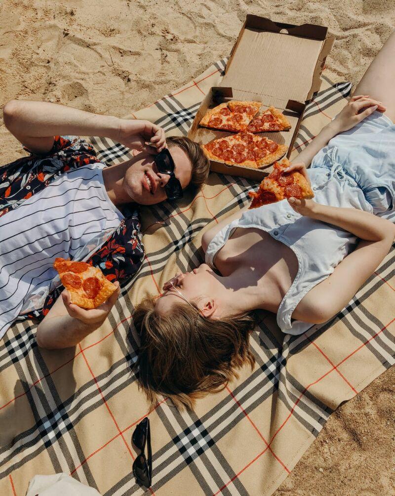 Парень с девушкой едят на пляже пиццу