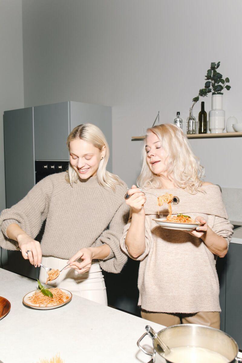 Женщины едят спагетти