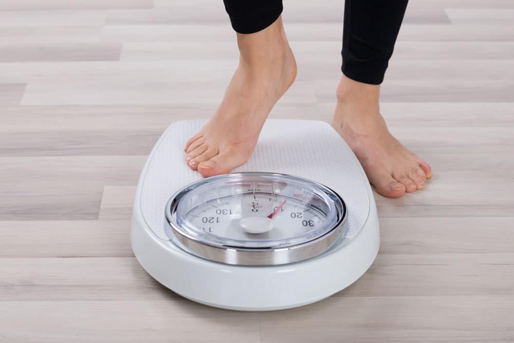 Женщина встает на весы