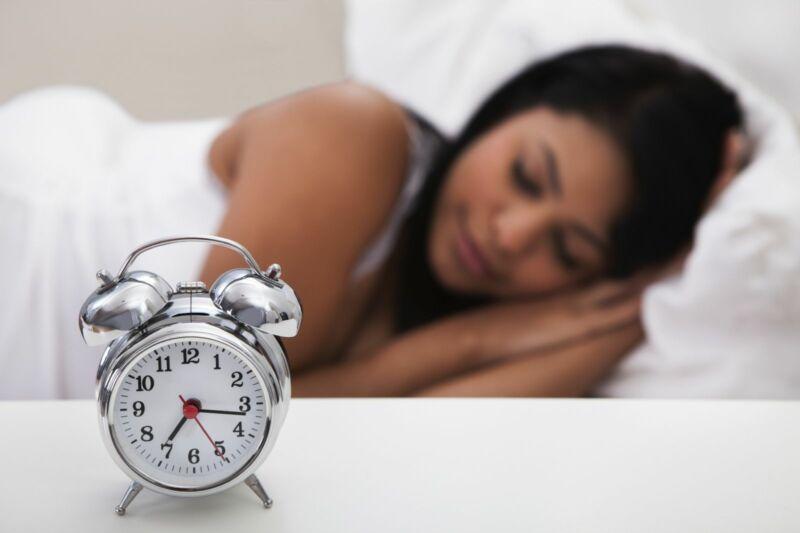 Часы и спящая женщина в кровати