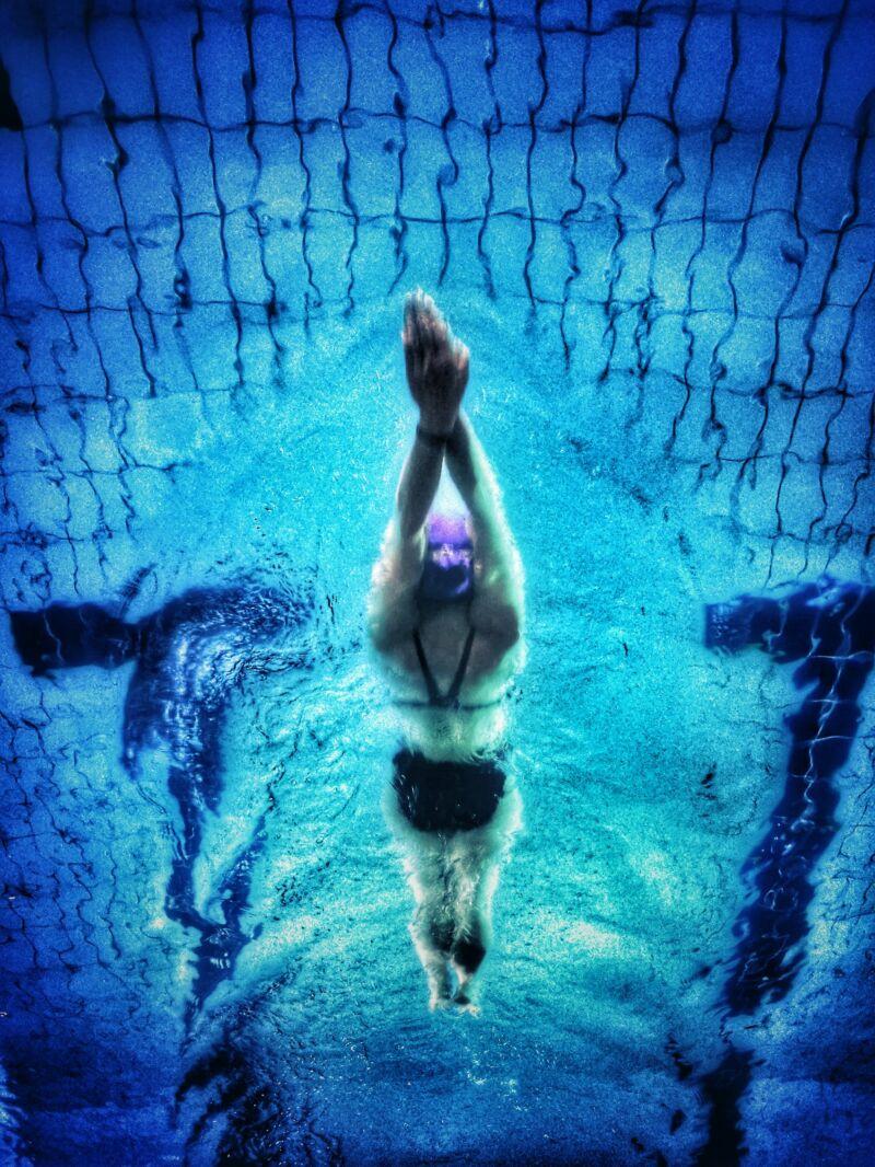 Женщина плывет в бассейне