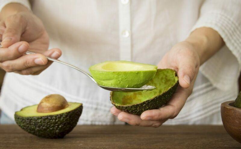 Женщина чистит авокадо