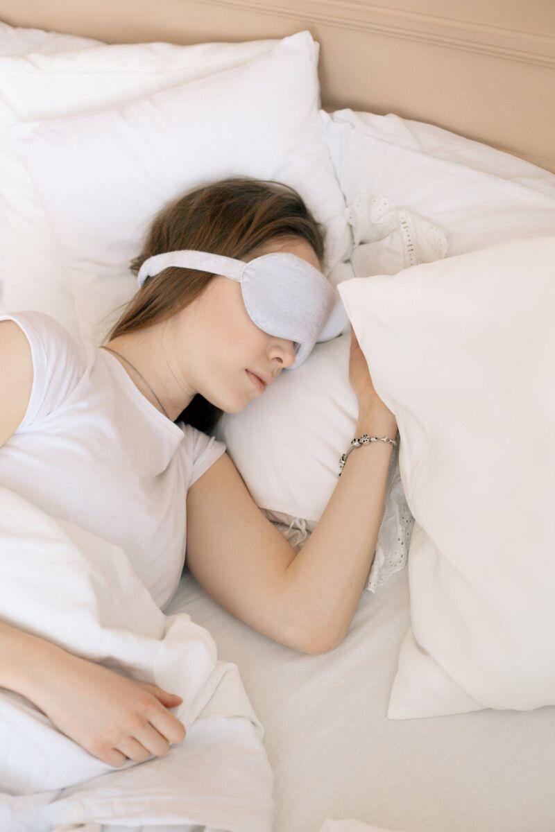 Женщина спит с повязкой для глаз