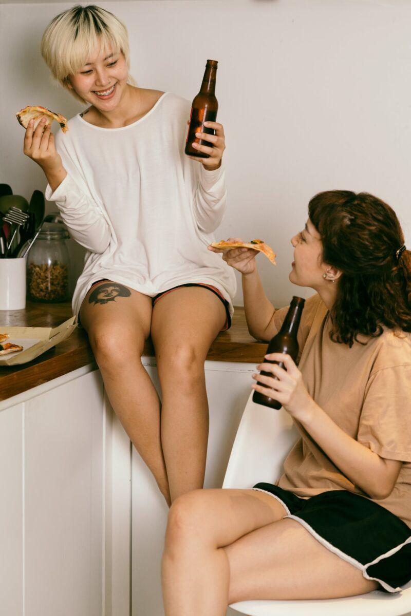 Девушки пьют пиво и едят пиццу