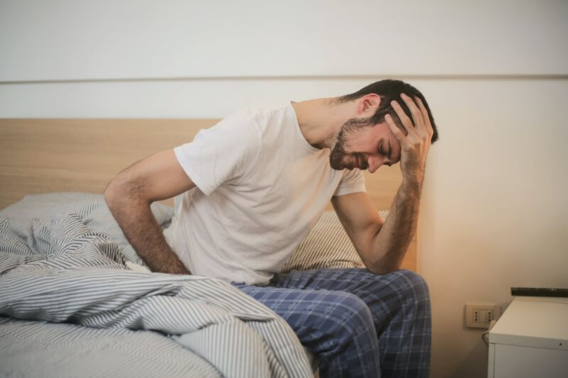 Мужчина с похмельем сидит на кровати