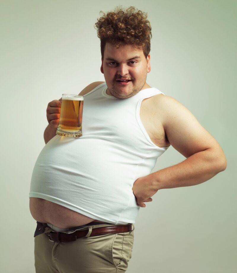 Мужчина с пивным животом держит бокал пива