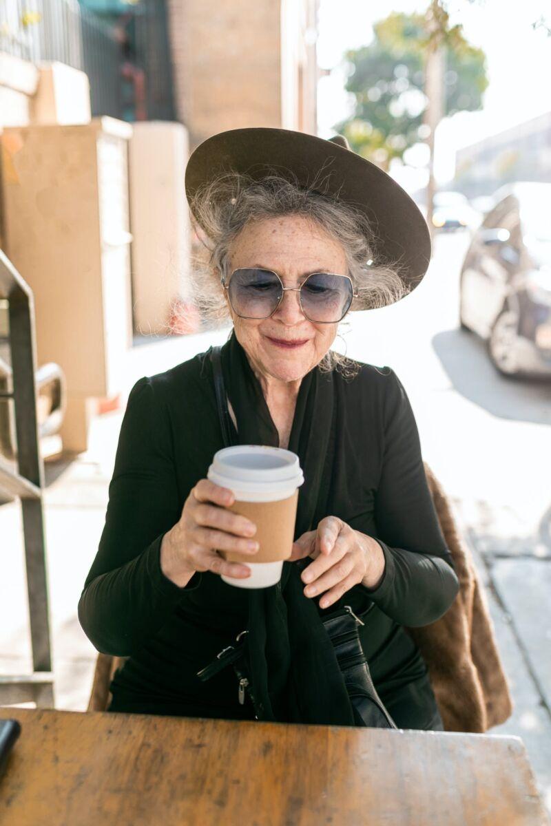 Старая женщина пьет кофе