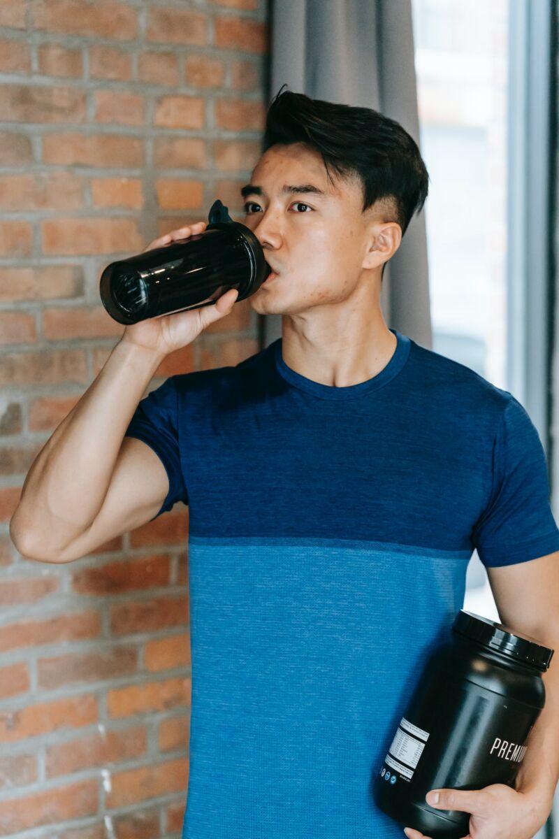 Мужчина пьет белковый напиток