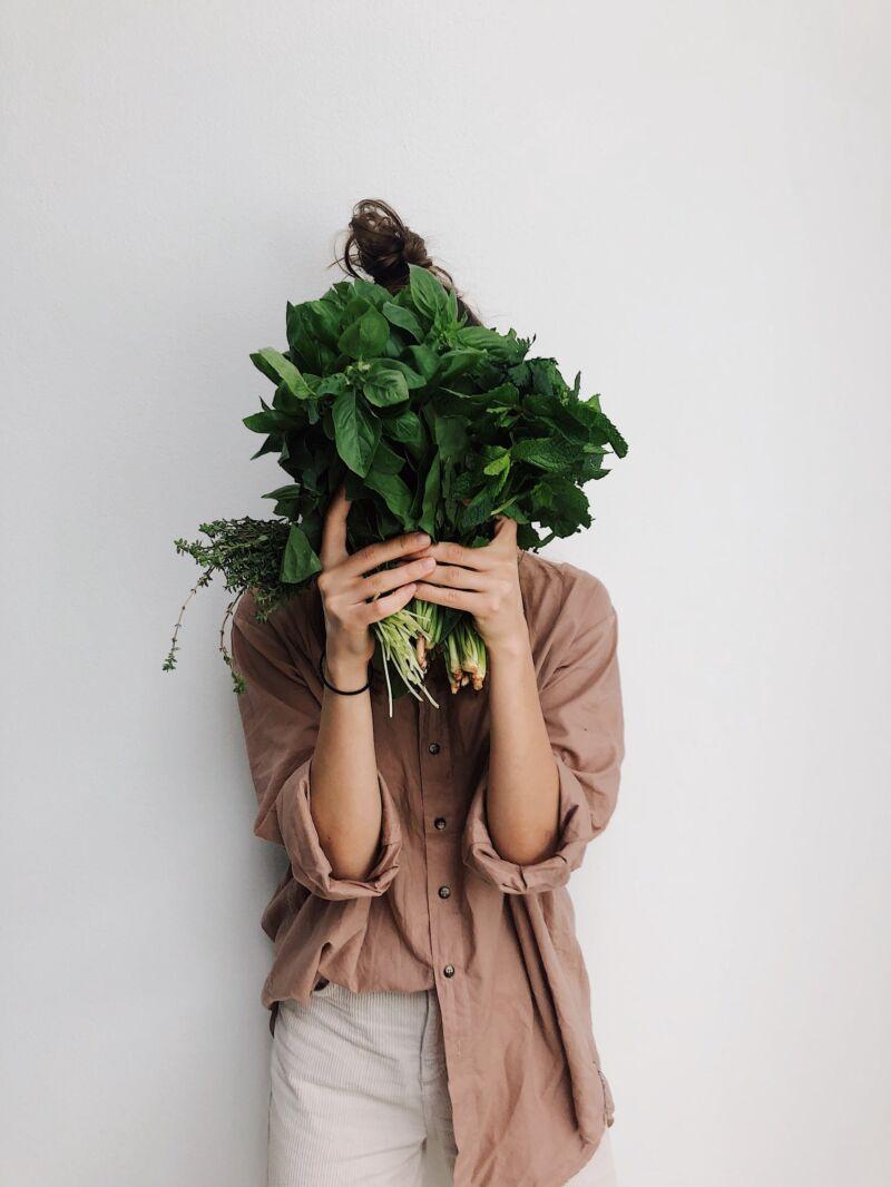 Женщина закрывает лицо зелеными овощами