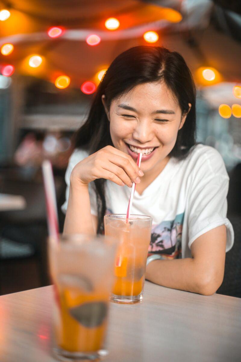 Женщина пьет алкогольный коктейль