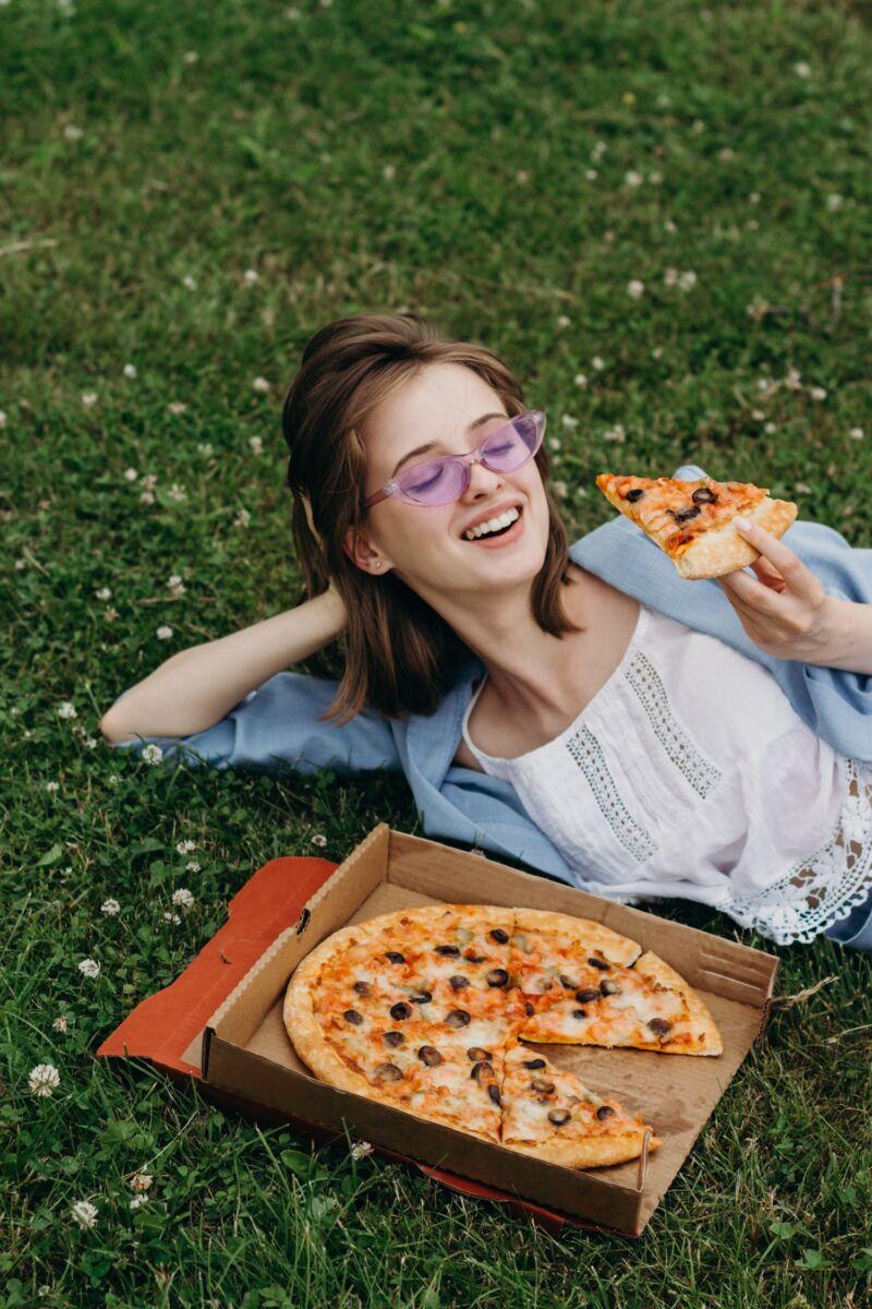 Девушка лежит на траве и ест пиццу
