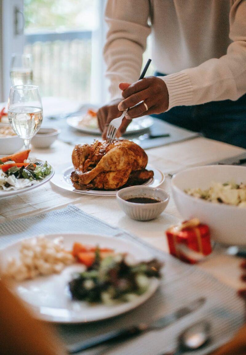 Мужчина берет курицу на столе
