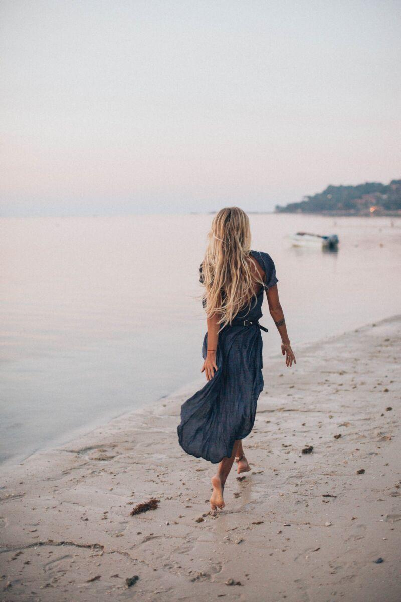 Женщина гуляет по пляжу