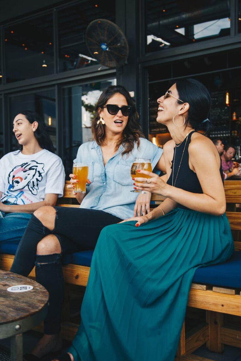 Женщины сидят на скамье и пьют пиво